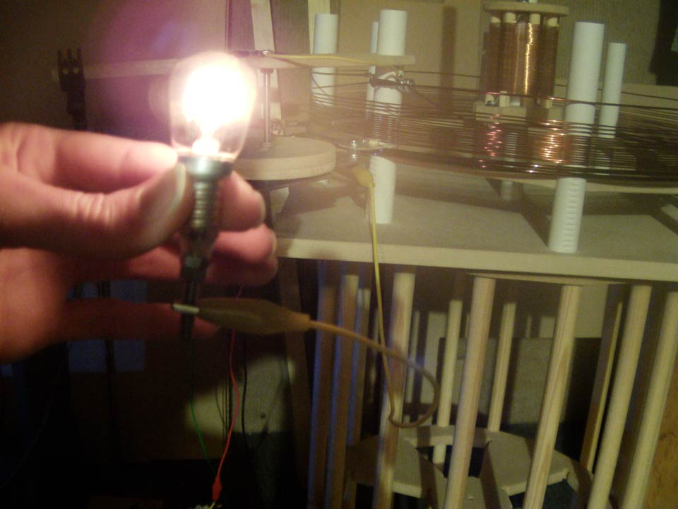 Single wire power transmission – Holding and lighting an incandescent bulb powered from the ground terminal of an 1860 kc scale model Tesla Magnifying Transmitter